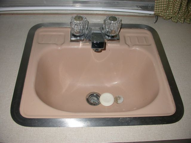 original coral pink bathroom sink with replacement faucet and taps by